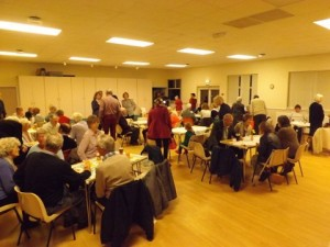 People meeting at the village hall for a traditional supper after the service